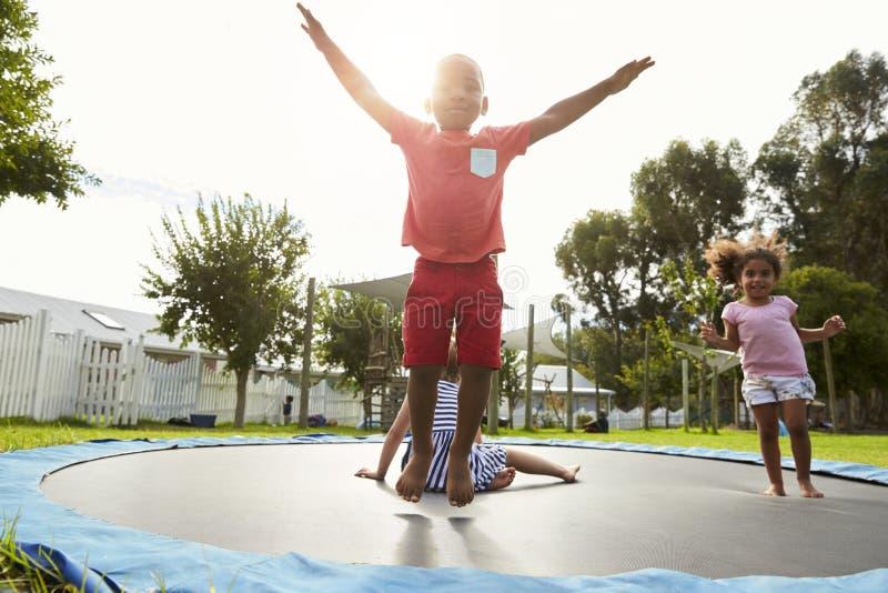 孩子在获得蒙台梭利的学校在室外绷床的乐趣 免版税图库摄影