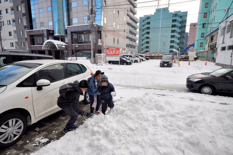 孩子在路附近一起演奏雪并且修造作为bac 库存照片