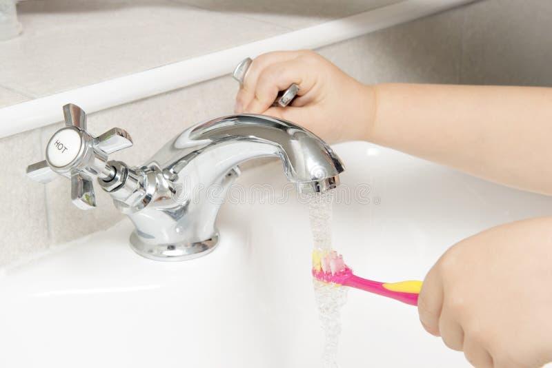 孩子在连续卫生间水槽水中的漂洗牙刷 库存照片
