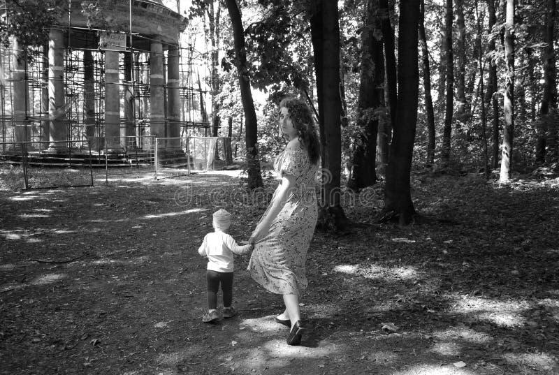 孩子在道路的公园今后拉扯她的母亲,拿着她由sundress的吊边 r 免版税库存图片