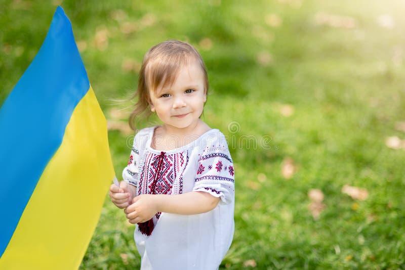 孩子在野外携带飘扬的乌克兰蓝黄旗 乌克兰的独立日 标志日 宪法日 女孩I 免版税库存图片