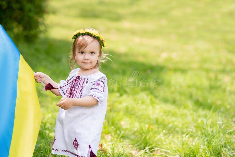 孩子在野外携带飘扬的乌克兰蓝黄旗 乌克兰的独立日 标志日 宪法日 女孩I 图库摄影