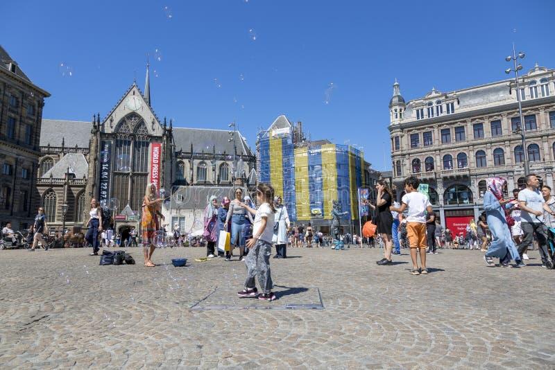 孩子在阿姆斯特丹捉住在中央水坝正方形的肥皂泡 库存照片