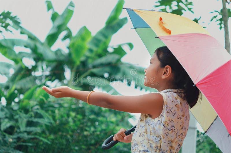 孩子在雨中获得使用的乐趣在公园有伞 免版税库存照片