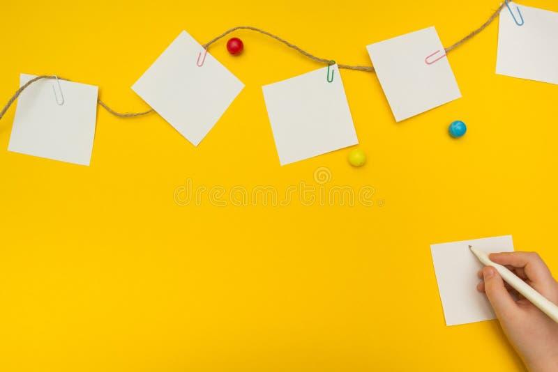 孩子在黄色背景写笔记 本文笔记 免版税库存照片