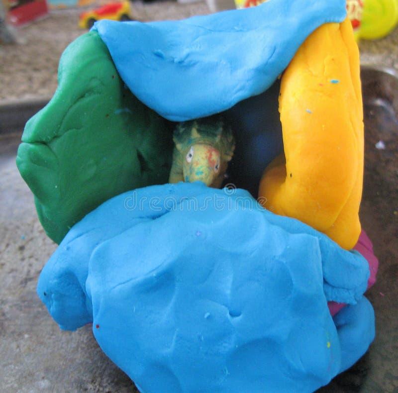孩子在黏土洞的工艺恐龙 免版税库存照片