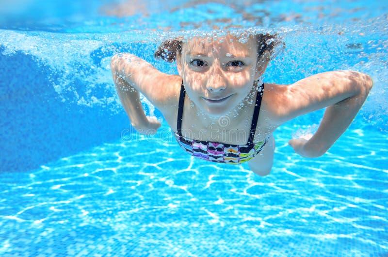 孩子在水池游泳在水面下 图库摄影