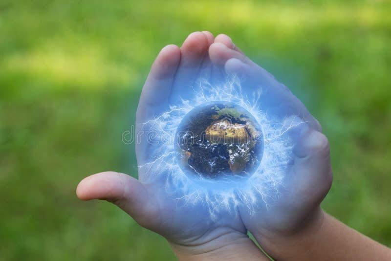 孩子在他的手上拿着地球 库存照片