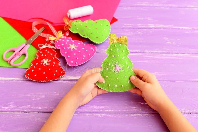 孩子在他的手上的拿着圣诞树玩具 显示圣诞节工艺的孩子 毛毡制作孩子的想法 剪刀,螺纹 免版税库存照片