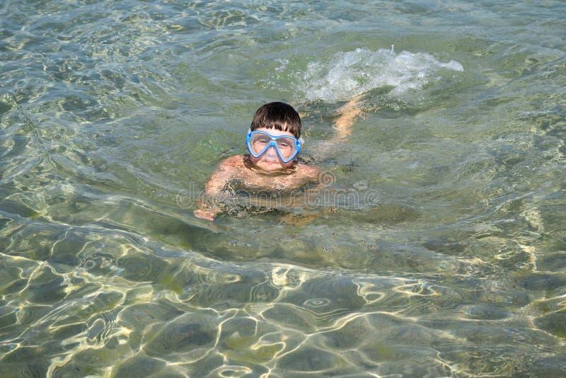 孩子在水肺面具游泳在海 库存照片