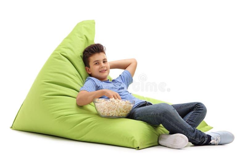 孩子坐一个舒适的装豆子小布袋 免版税库存图片