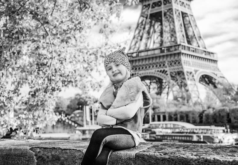 孩子坐在堤防的栏杆在埃佛尔铁塔附近 免版税库存照片