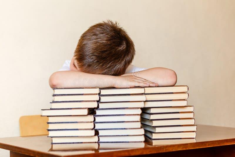孩子坐在桌上,把他的头放在书上 免版税库存照片