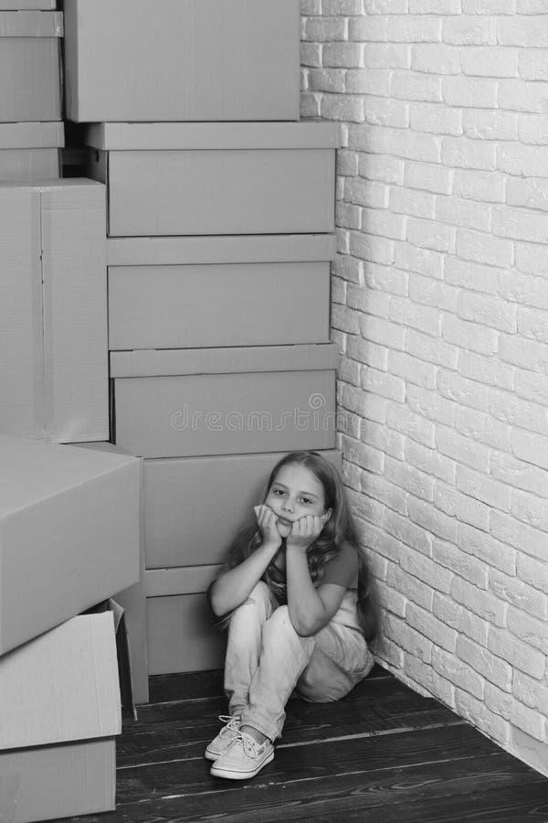 孩子坐在角落的地板 在纸板箱中的孩子 免版税库存图片