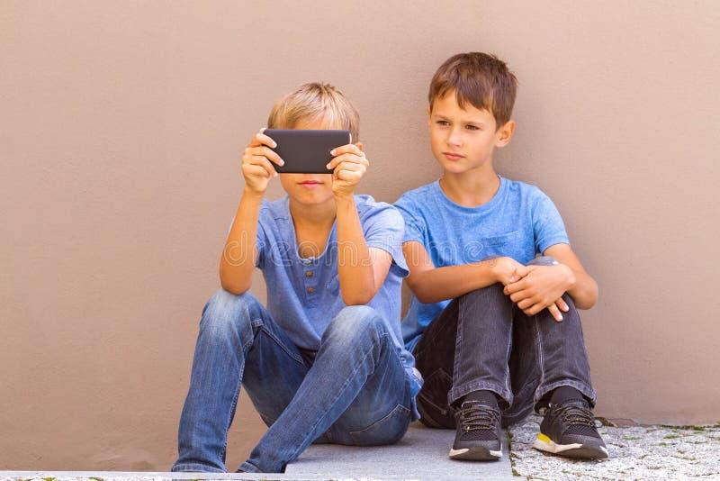 孩子坐外部和打比赛在智能手机 图库摄影