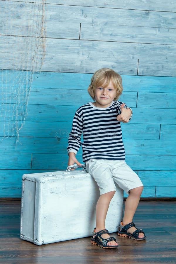孩子坐手提箱 免版税库存图片