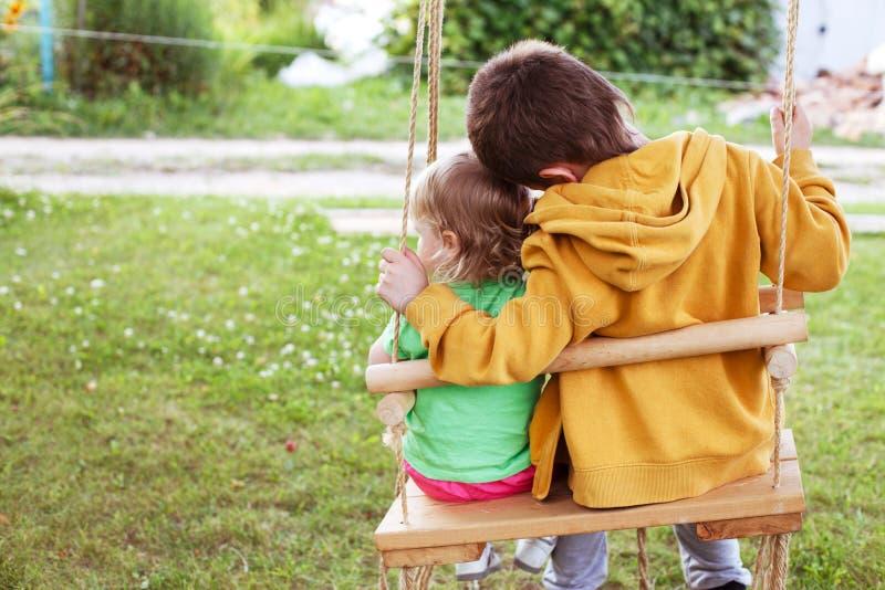 孩子坐摇摆在庭院里 免版税库存照片