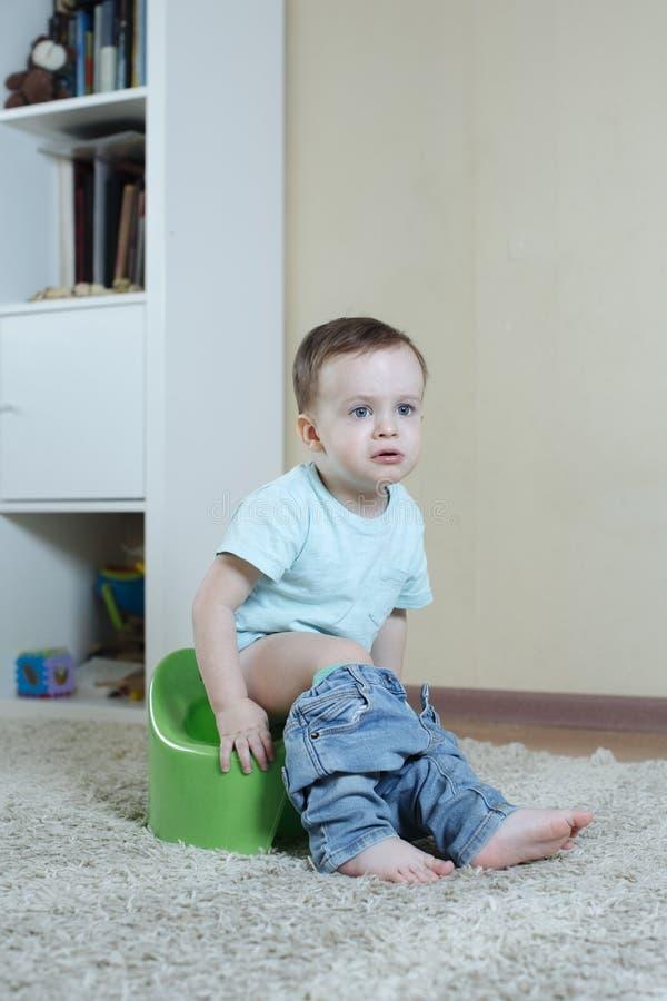 孩子坐有下来牛仔裤的一个罐并且是怏怏不乐对于某事 库存图片
