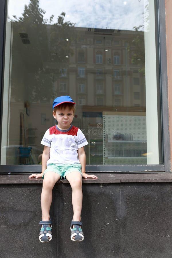 孩子坐窗台 免版税库存图片