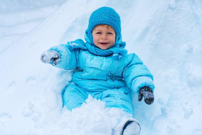 孩子坐雪 免版税库存图片
