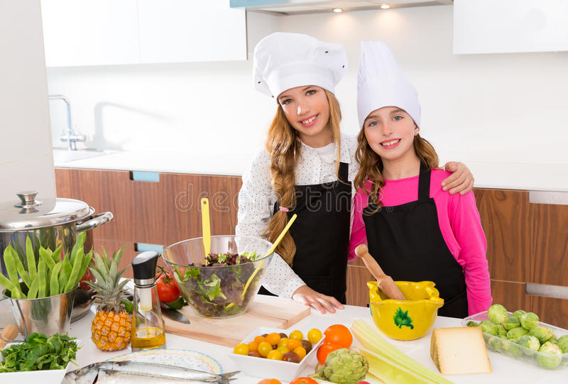 孩子女孩小辈厨师朋友一起拥抱在烹调学校 免版税库存图片