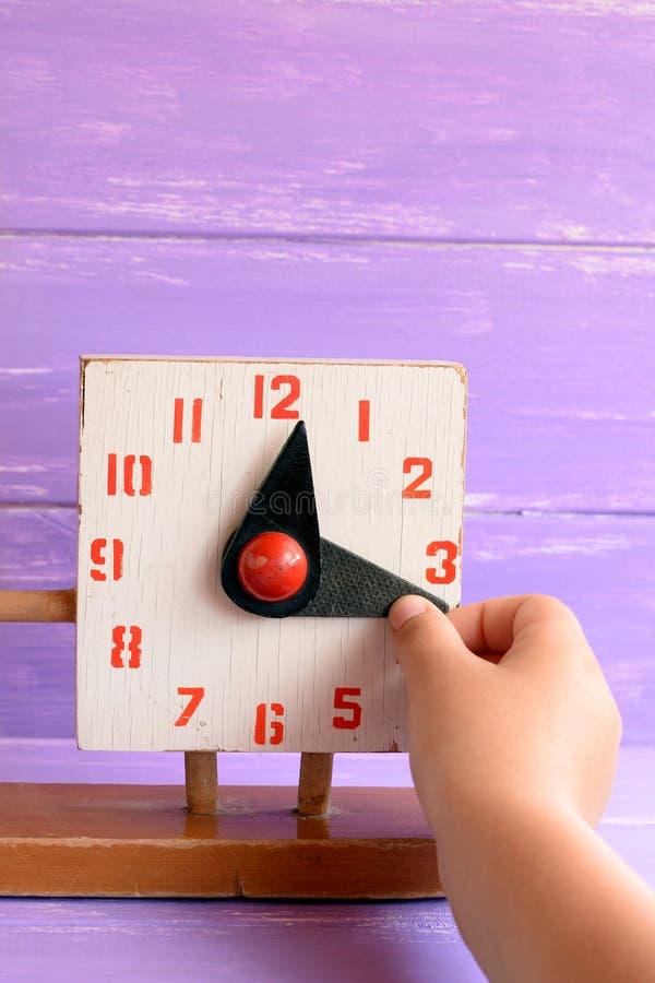 孩子学会告诉在老木时钟玩具的时间 孩子拉扯手翻译时间 免版税图库摄影