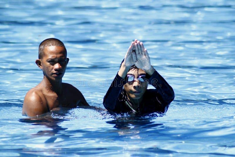 孩子学会如何在游泳教练帮助下游泳 免版税库存照片