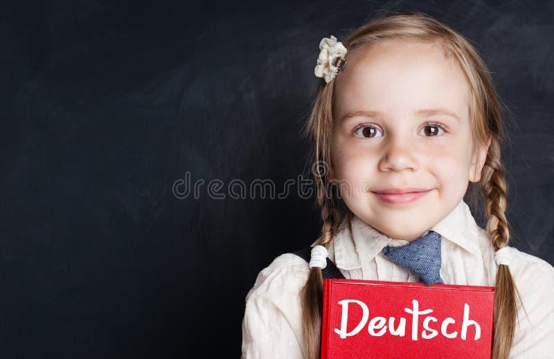 孩子学会德语 有德国书的好奇儿童女孩 免版税库存照片