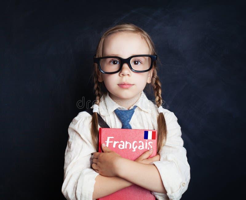 孩子学会法语 有法国书的聪明的儿童女孩 免版税库存图片