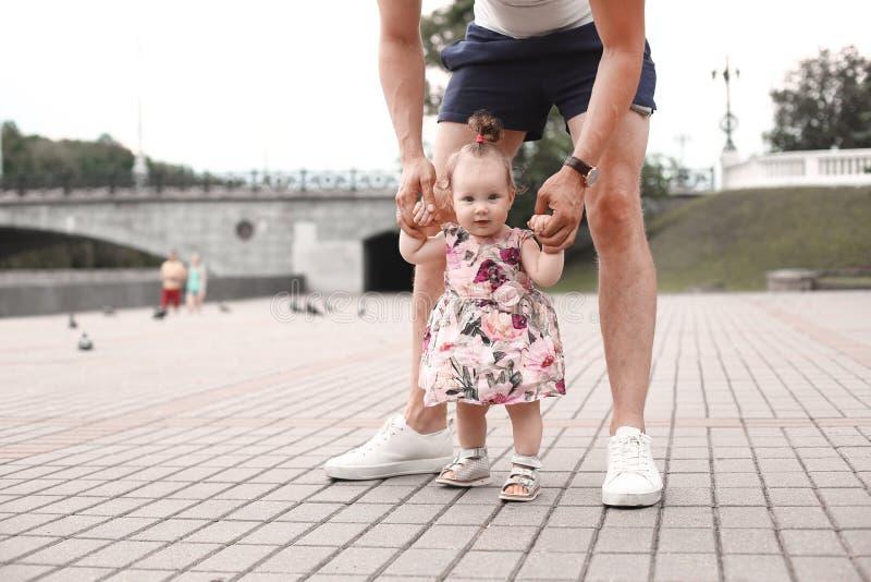 孩子学会走 父亲支持孩子并且教他走 免版税库存图片