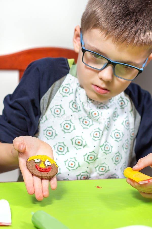 孩子完成的工作 孩子装饰的桂香回合曲奇饼 笑容绘与五颜六色的被冰的毡尖的笔 免版税图库摄影