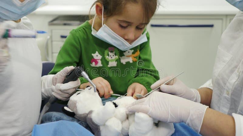 孩子对待玩具与牙医使用不同的牙齿工具 库存图片