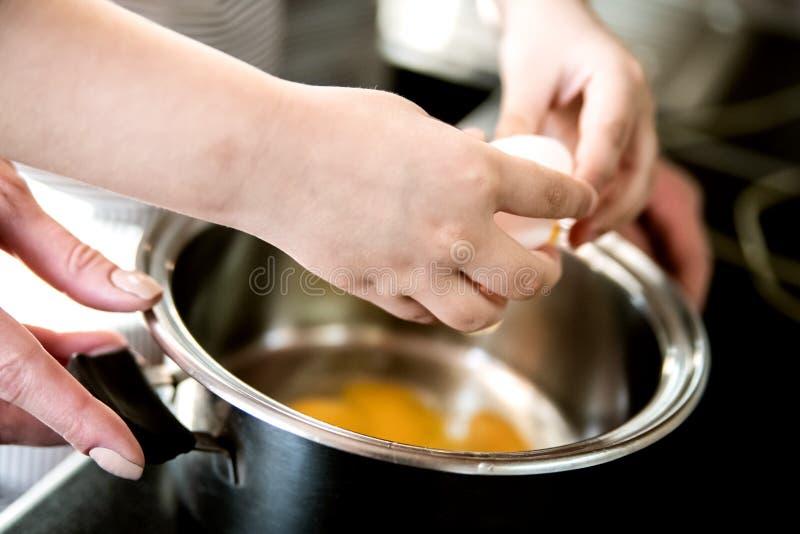 孩子帮助妈妈厨师早餐并且闯进鸡蛋平底深锅 免版税库存图片