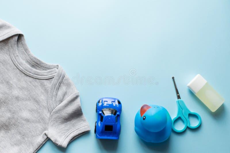 孩子平展放置与文本的衣裳蓝色背景顶视图空间 蓝色汽车,鸭子,油 免版税库存图片