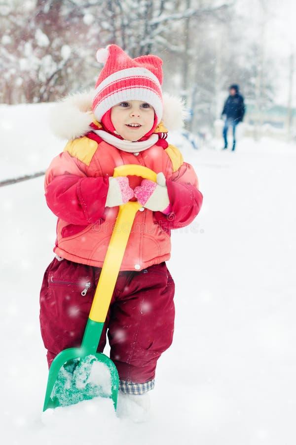 孩子开掘雪铁锹 库存图片