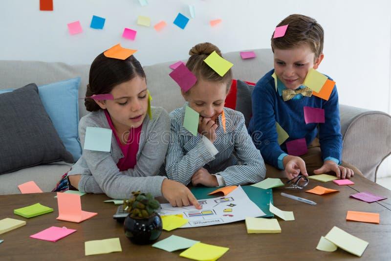 孩子当使用与稠粘的笔记的商业主管 免版税库存照片