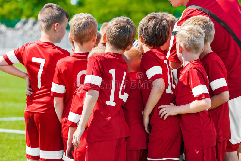 孩子戏剧体育 儿童站立与教练的体育队团结 库存图片