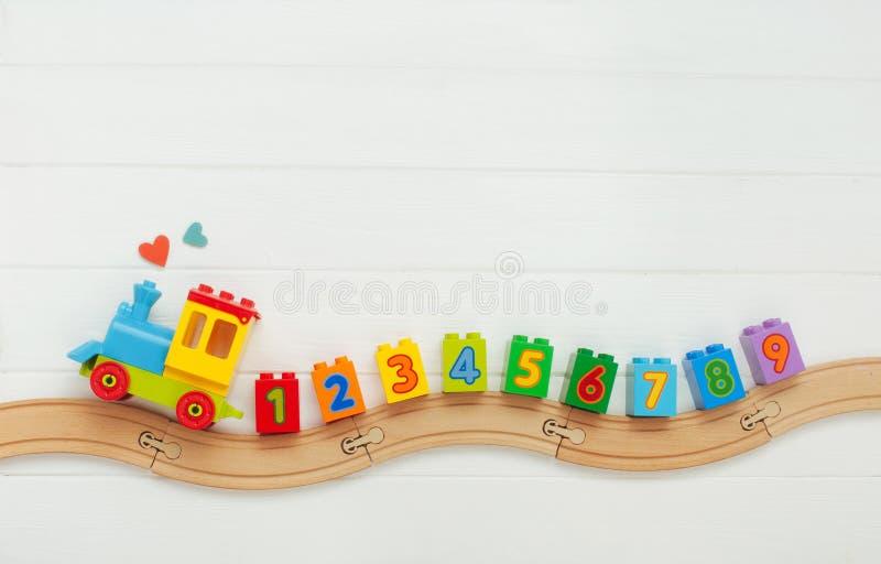 孩子戏弄有数字的火车在白色木背景的铁路与拷贝空间 免版税库存图片