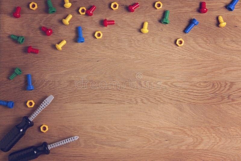 孩子戏弄背景有五颜六色的坚果、螺栓和两把螺丝刀的框架房客在木桌上 顶视图 平的位置 免版税库存照片