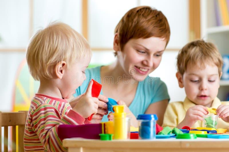 孩子或孩子和母亲演奏五颜六色的黏土玩具 库存照片