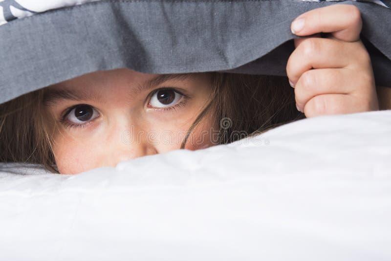 孩子或青少年的下面盖子在床上 库存图片