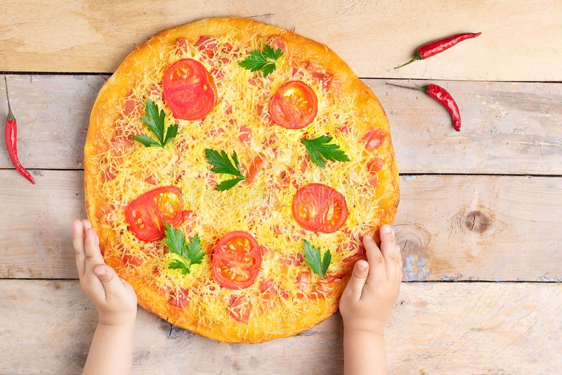 孩子手拿着乳酪玛格丽塔酒比萨用蕃茄和蓬蒿,在木土气桌上的素食主义者膳食,顶视图 库存照片