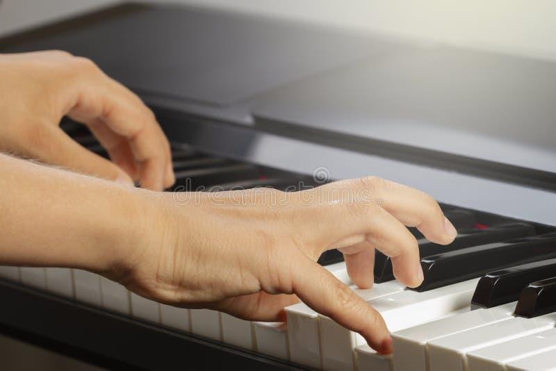 孩子手接近的看法使用在琴键的 免版税库存照片