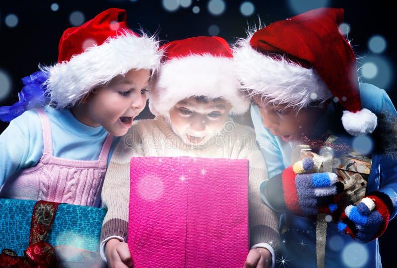 孩子打开一个不可思议的当前箱子 免版税库存照片