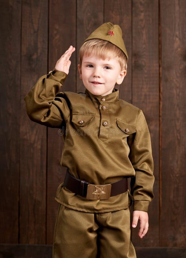 孩子打扮作为减速火箭的军服的战士 免版税图库摄影