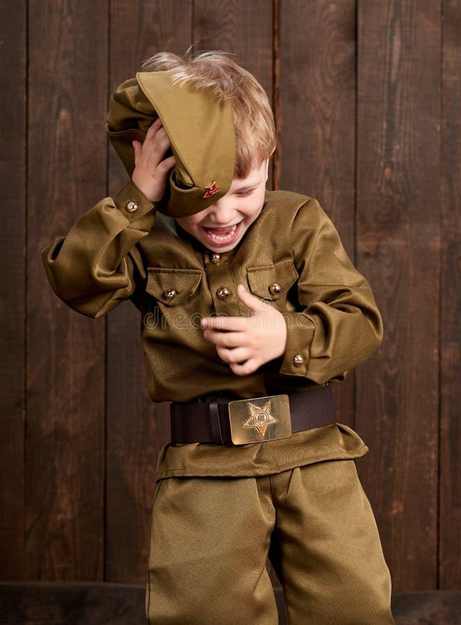 孩子打扮作为减速火箭的军服的战士 库存照片
