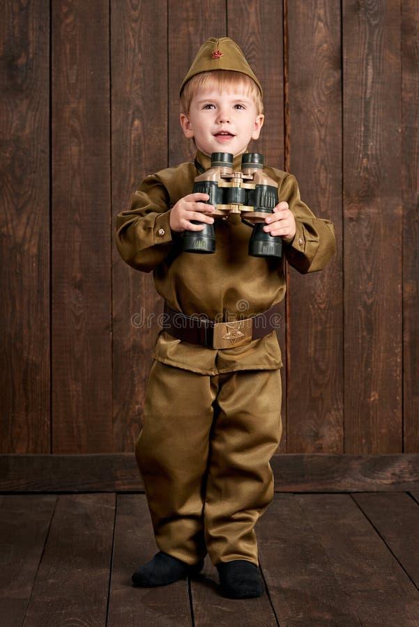 孩子打扮作为减速火箭的军服的战士 库存图片