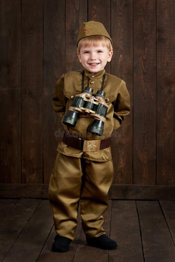 孩子打扮作为减速火箭的军服的战士 免版税库存图片