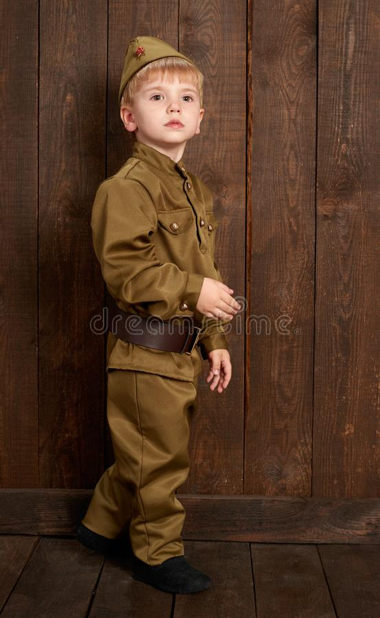 孩子打扮作为减速火箭的军服的战士 图库摄影
