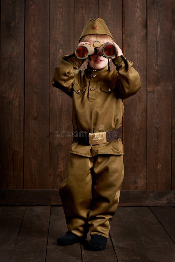 孩子打扮作为减速火箭的军服的战士 免版税库存照片